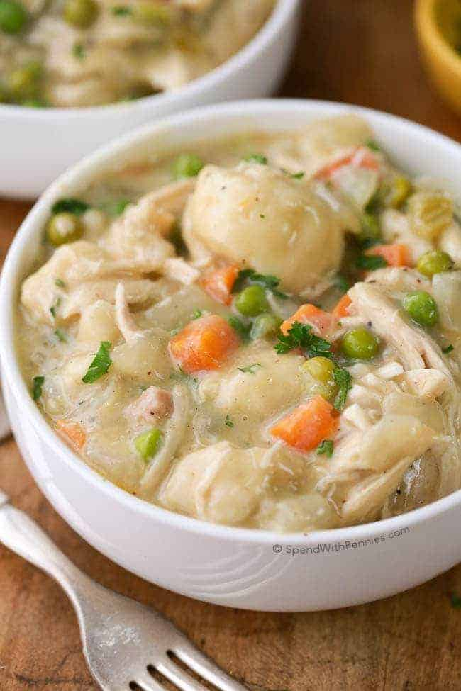 Crockpot chicken and dumplings with carrots, peas and parsley garnish in a white bowl with a fork