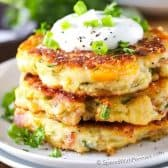 Loaded Mashed Potato Cakes with sour cream and green onions and parsley in the background on a wood table