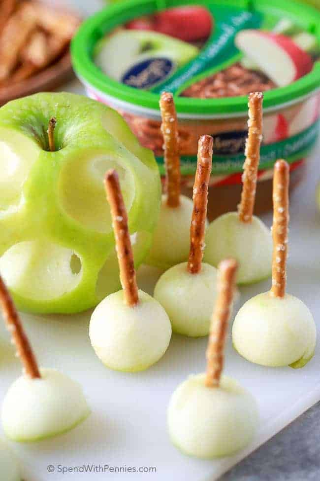 mini caramel dippers cut from an apple with pretzels in them