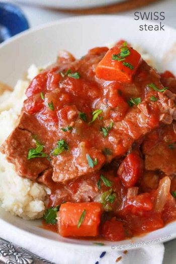 Swiss Steak over mashed potatoes in a bowl topped with parsley