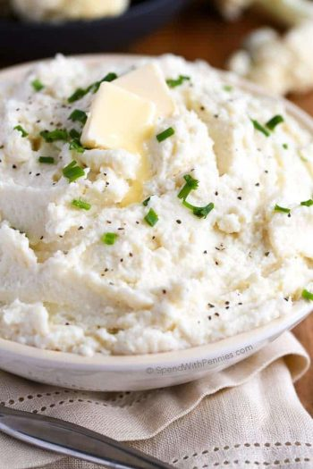 mashed cauliflower in a large serving bowl with garnish on top