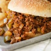Slow Cooker Sloppy Joes served on a bun on a tray with chips
