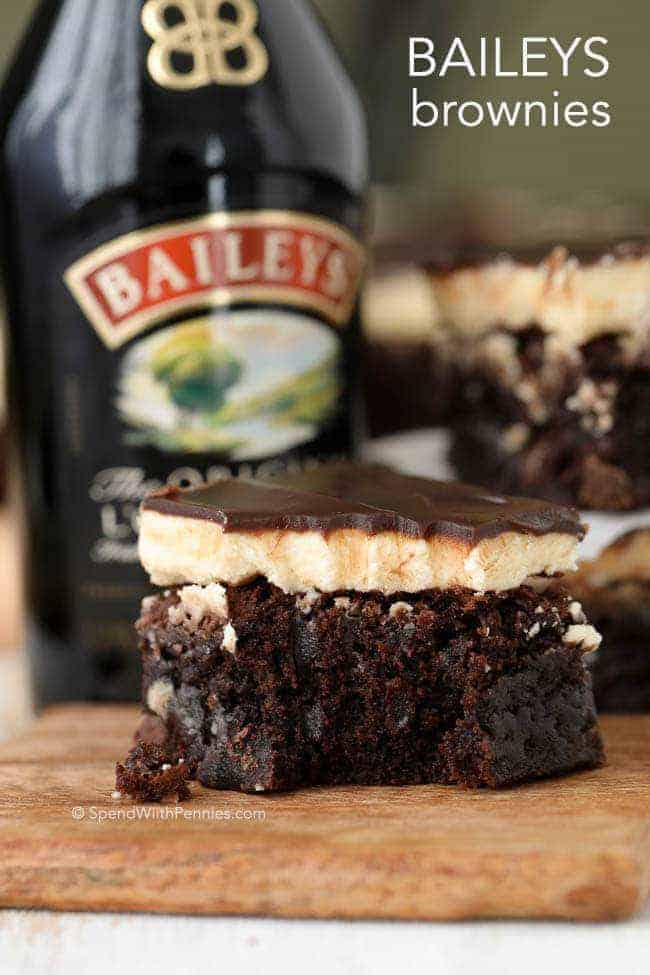 Rich, fudgy baileys brownies on a wooden board with a bottle of Baileys in the background