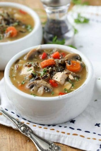 Chicken Wild Rice Soup with carrots and mushrooms with pepper and parsley on a table