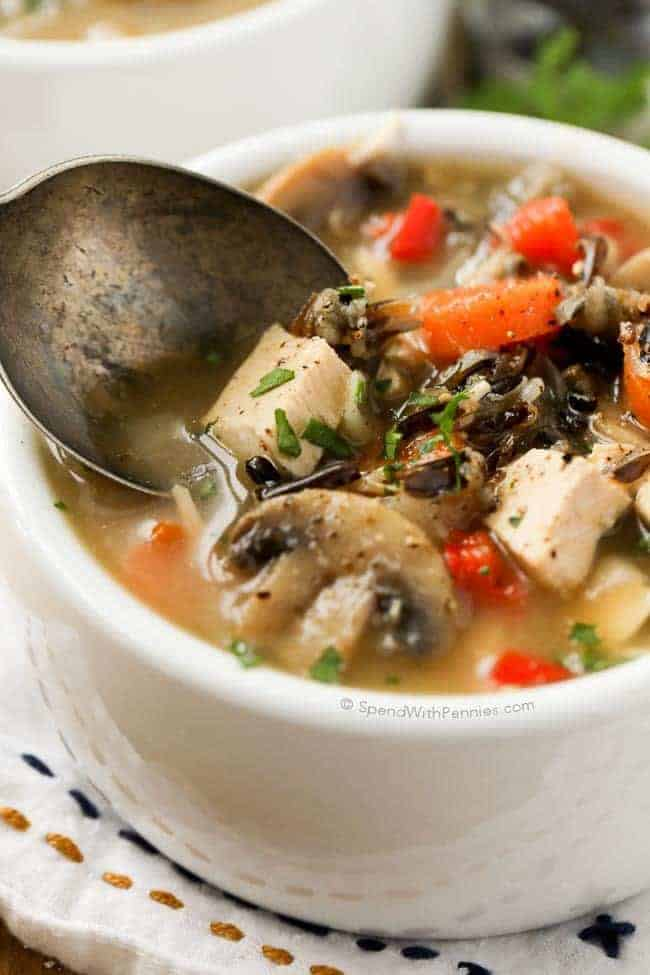 Chicken Wild Rice Soup with carrots and mushrooms being eaten with a spoon