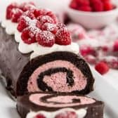 Raspberry Chocolate Swiss Roll topped with berries and a bowl of raspberries in the background
