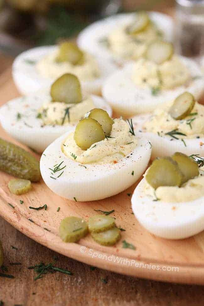 Dill Pickle Deviled Eggs garnished with pickle slices on a tray