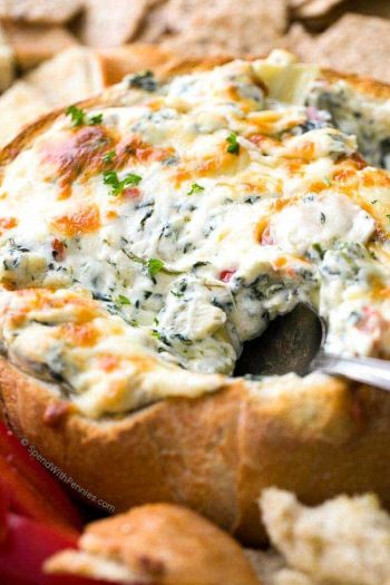 taking a spoonful of Hot Spinach and Artichoke Dip in a bread bowl