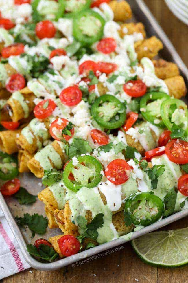 loaded taquitos with creamy jalapeño dip on a baking tray garnished with tomatoes, jalapeños and cheese