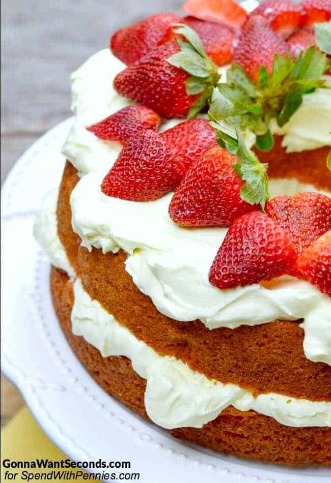 Strawberries and Cream Cake is a fluffy pink Strawberry cake with a rich creamy topping and garnished with fresh strawberries! This cake is a pretty and delicious as it is easy to make.