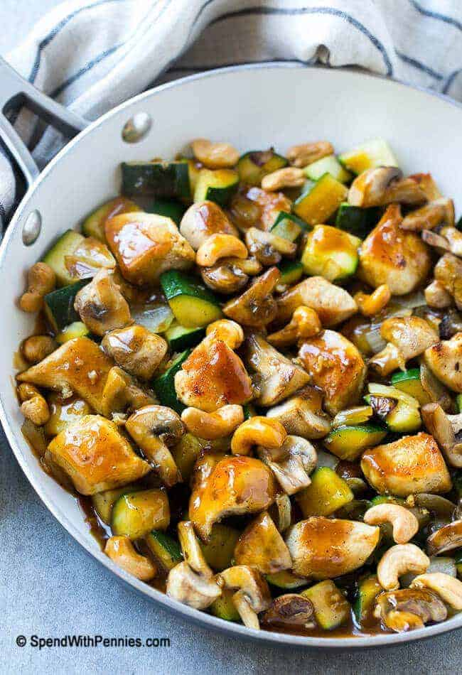 cashew chicken stir fry full of sauteed chicken, veggies and crunchy cashews, coated in a simple savory sauce in a skillet
