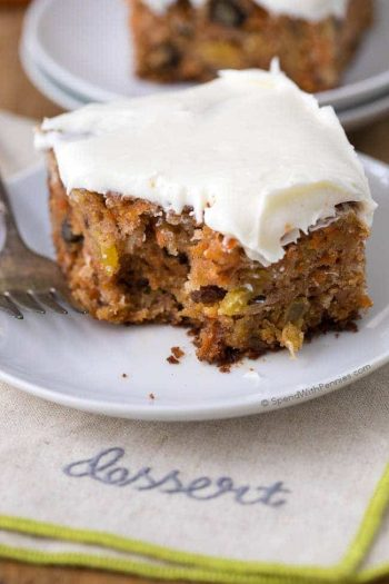 homemade carrot cake with frosting on white plate
