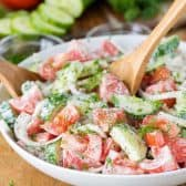 Creamy Cucumber Tomato Salad in a white bowl with wooden spoons