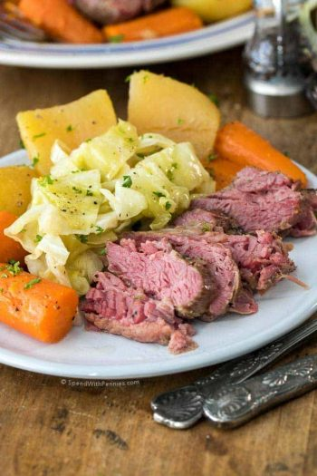 Corned beef and cabbage with potaots and carrots on a white plate