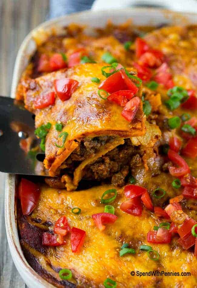 beef enchilada casserole being served with a silver spatula from a baking dish