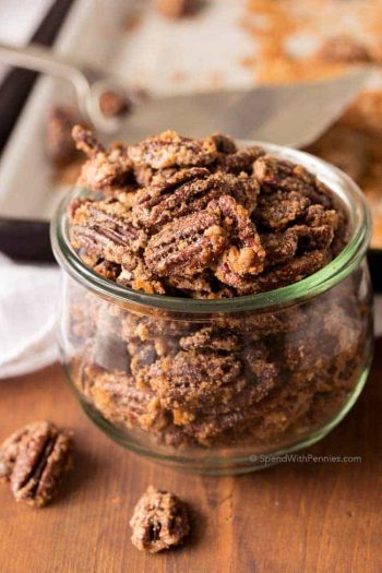 candied pecans in a glass dish with a couple of pecans in front