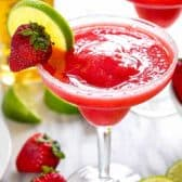 strawberry margarita garnished with lime and strawberry in a margarita glass
