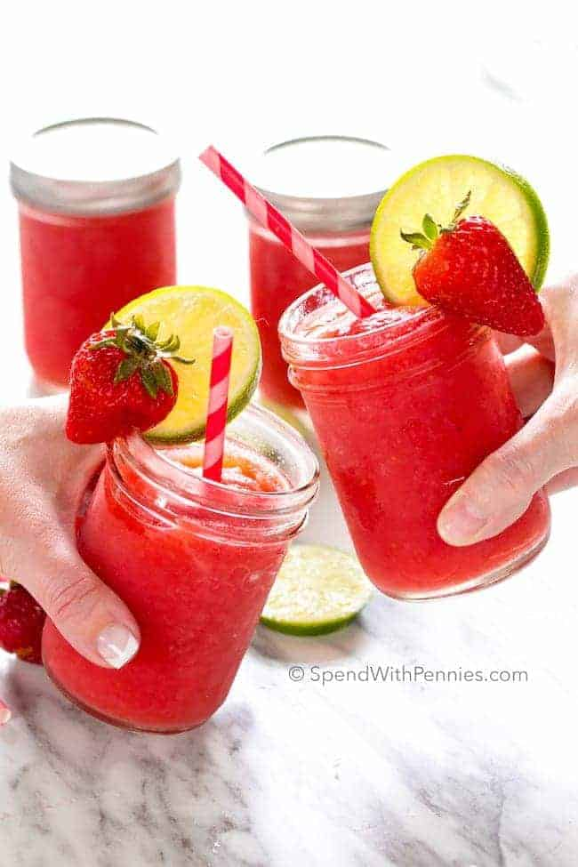 cheers with two strawberry margaritas in mason jars