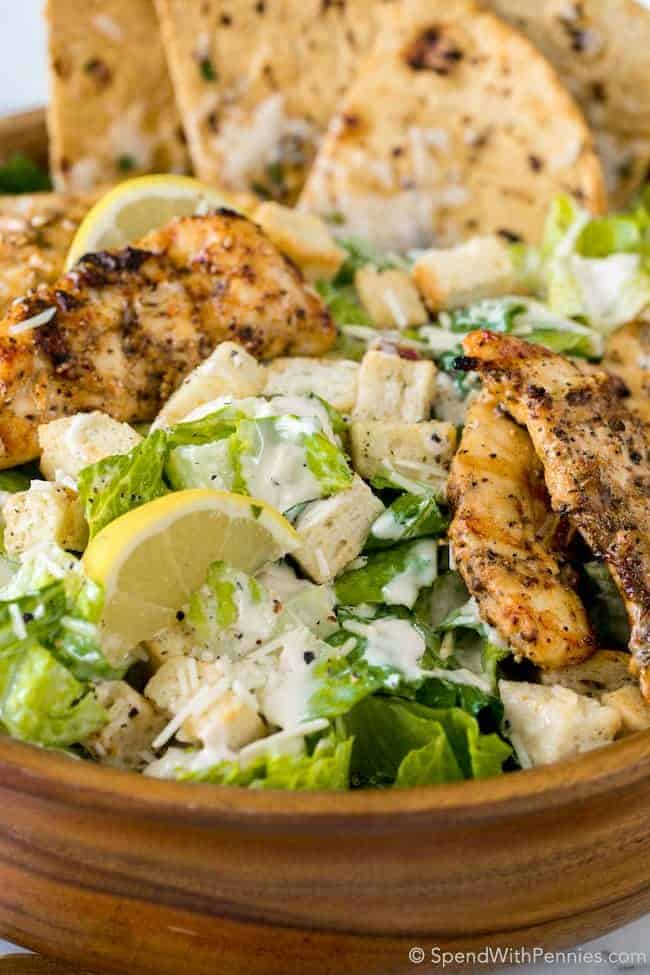 Chicken Caesar Salad with Grilled Flatbread is the perfect summer meal! Juicy chicken, crisp fresh lettuce with a creamy garlic parmesan dressing all topped off with a grilled garlic parmesan flatbread.