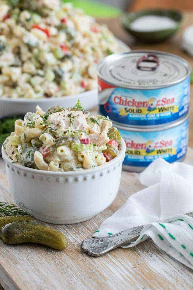 Pickled Tuna Macaroni Salad in a white bowl with tuna in the background