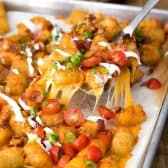 serving up Tater Tot Nachos garnished with green onion and tomatoes, from a baking tray