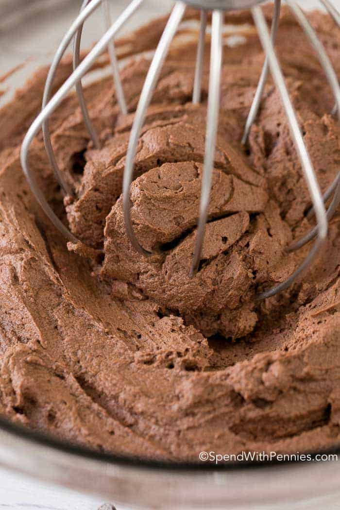 Stirring a clear glass bowl of Chocolate Ganache Frosting with a whisk