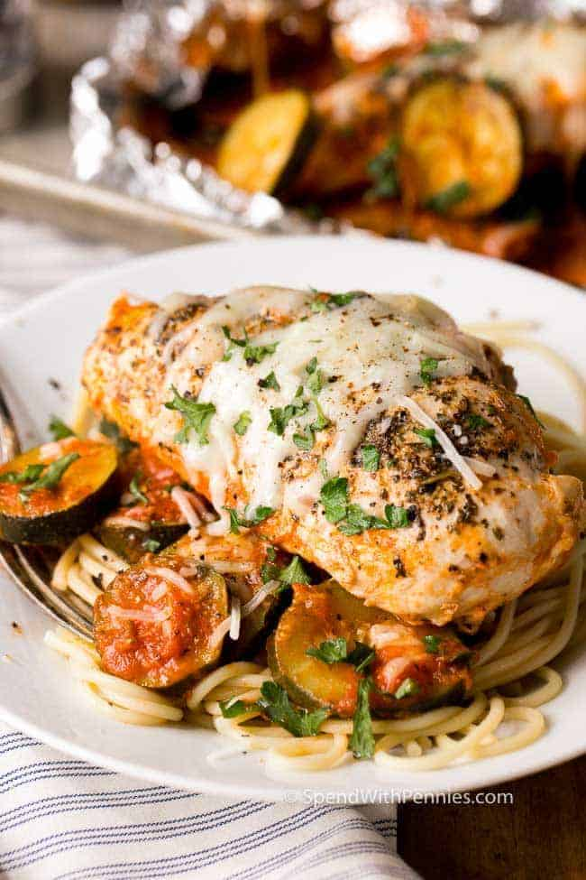 Serve these Parmesan Chicken Foil Packets over spaghetti for feed a hungry crowd! This easy meal contains all of your toppings in one tidy little packet!  Fresh summer zucchini, zesty tomato sauce and tender chicken breasts are grilled until perfectly cooked and topped with melty mozzarella cheese.  This is going to become your favorite summer meal!