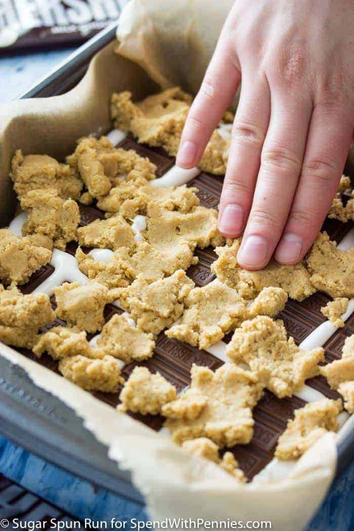 S'mores Bars with graham cracker crumb cookie layer being pressed in to chocolate bars