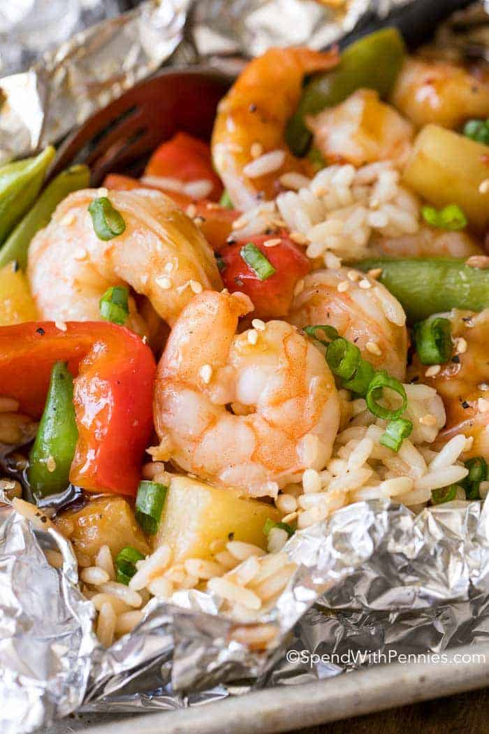pineapple teriyaki shrimp foil packet with peppers, pineapple and rice with green onion garnish