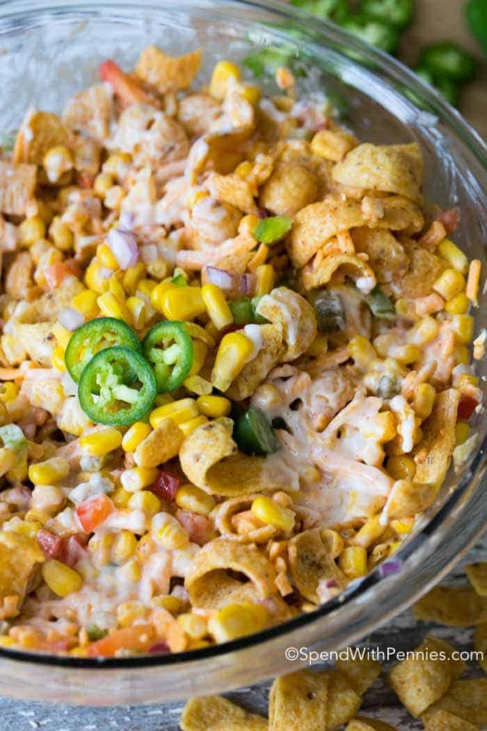 Frito Corn Salad combines sweet juicy corn, fresh bell peppers, spicy jalapenos and of course crunchy Fritos all in a creamy dressing.  This is the perfect potluck side dish or appetizer dip!