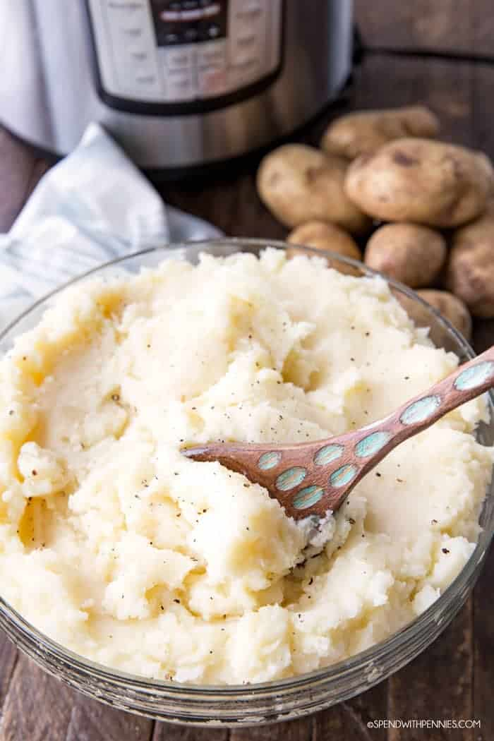 A bowl of mashed potatoes with a wooden spoon.