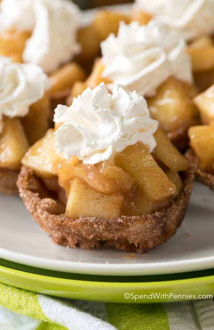 Apple Pie Bites are a quick and easy way to get your apple pie fix in a delicious hand held bite! Crisp cinnamon sugar shells are filled with a warm apple pie filling and topped with whipped cream or ice cream; the perfect fall bite.