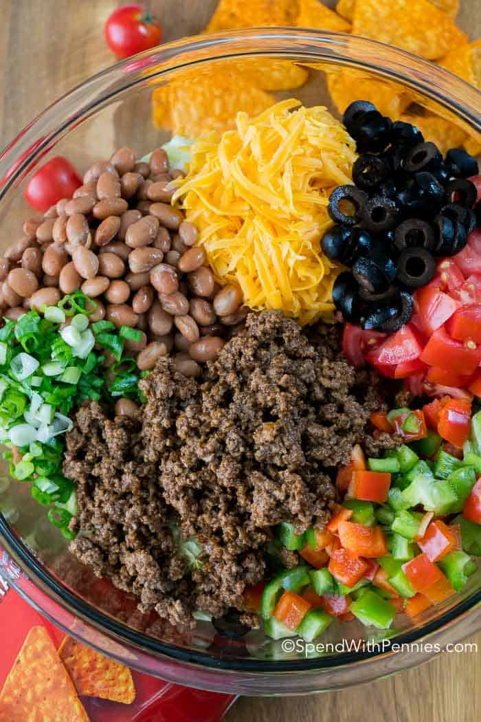 I have been asked for this recipe countless times! Dorito Taco Salad has loads of seasoned ground beef, veggies, beans and Doritos in a zesty sauce!