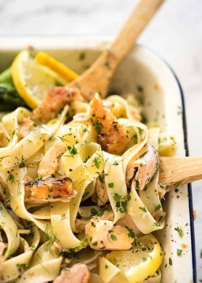 Lemon Butter Salmon Pasta in a baking dish with two wooden spoons