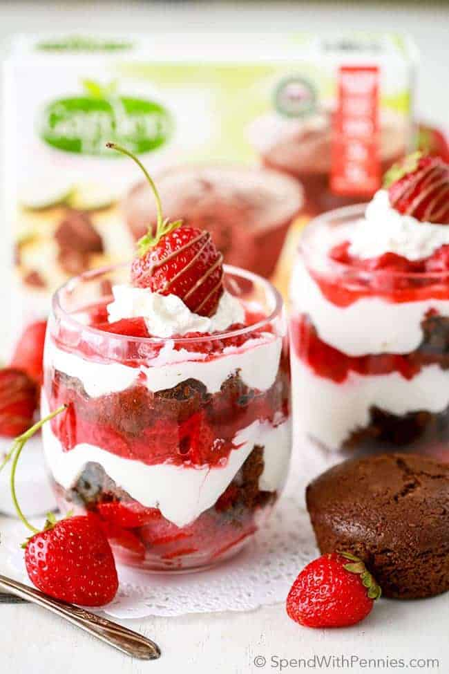 A glass mug filled with strawberry chocolate parfait, with a package of chocolate cupcakes in the background