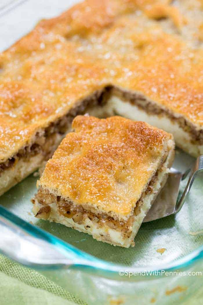 baklava cheesecake in baking dish with a square cut out