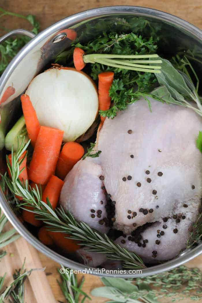 raw chicken, vegetables and herbs in a pot