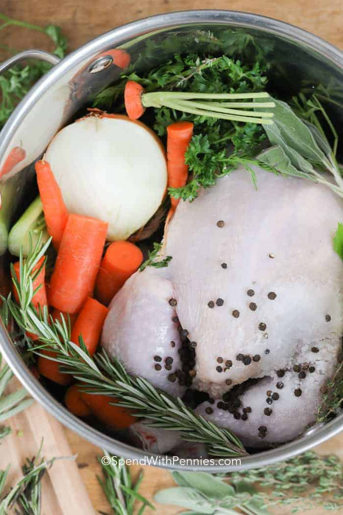 Raw chicken, herbs, onions and carrots in a stock pot to make boiled chicken