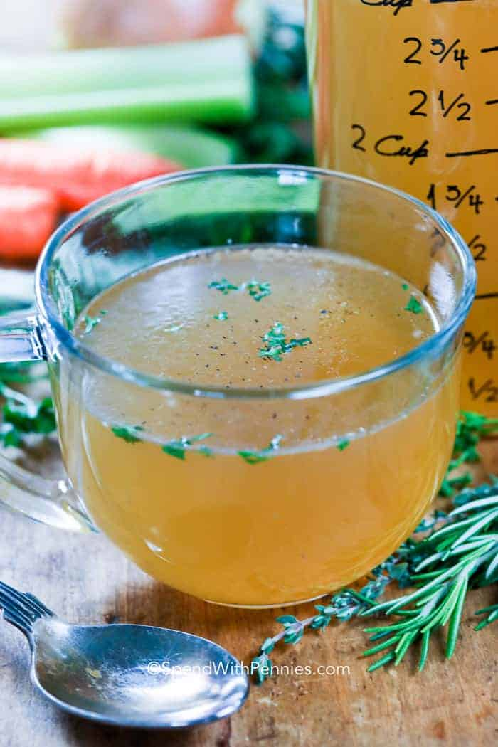 A cup of chicken stock with herbs