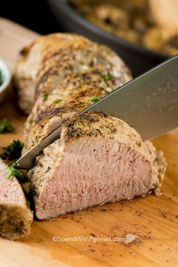 knife cutting into pork tenderloin