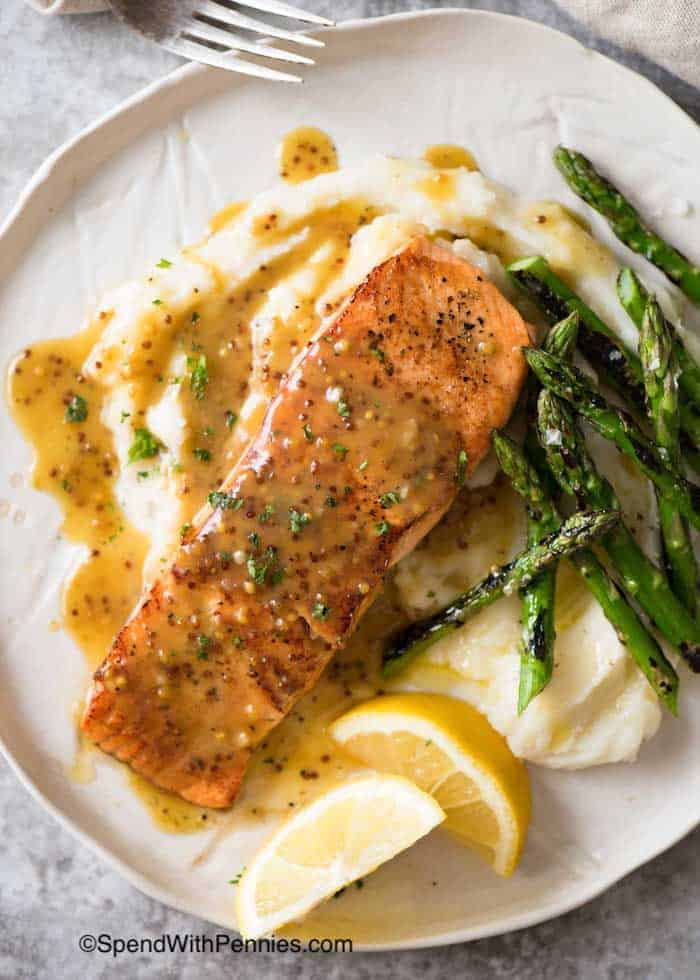 Honey Mustard Salmon on a white plate with asparagus, cauliflower and lemon wedges