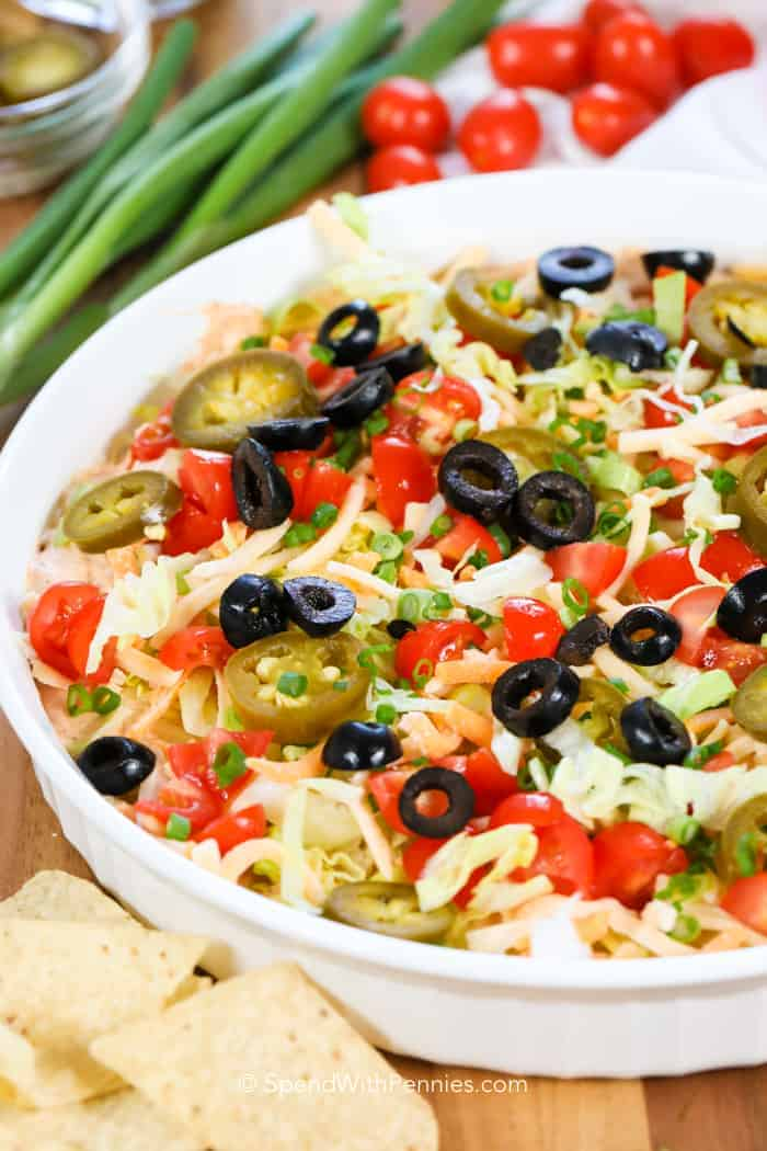 A quick 5 minute taco dip in a bowl topped with taco toppings including tomatoes, lettuce, jalapenos and olives