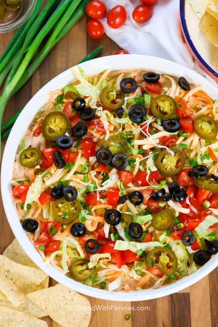 An overhead view of an easy taco dip topped with tomatoes, jalapenos and olives