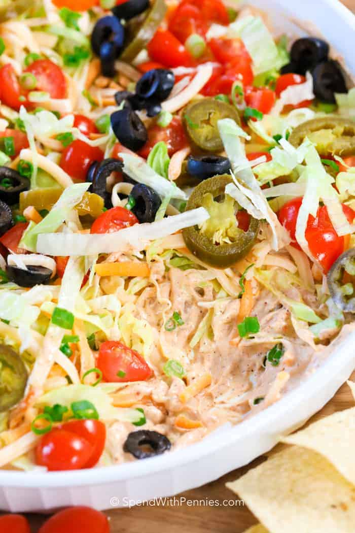 Close up photo of taco dip in a bowl with lettuce, tomatoes and jalapenos on top