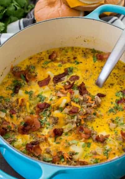 Bacon Cheeseburger Soup in a blue pot is a hearty and creamy take on America's favorite cheeseburger. The soup is full of flavor, easy to make and comforting.