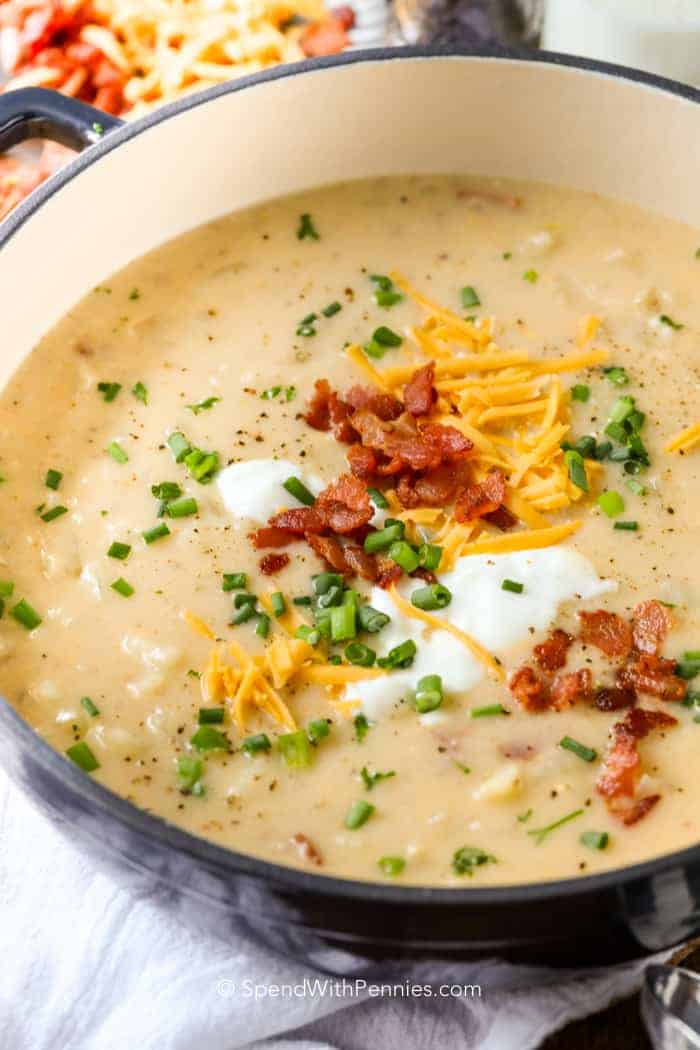 A large pot of baked potato soup topped with cheese, bacon, sour cream and green onions.