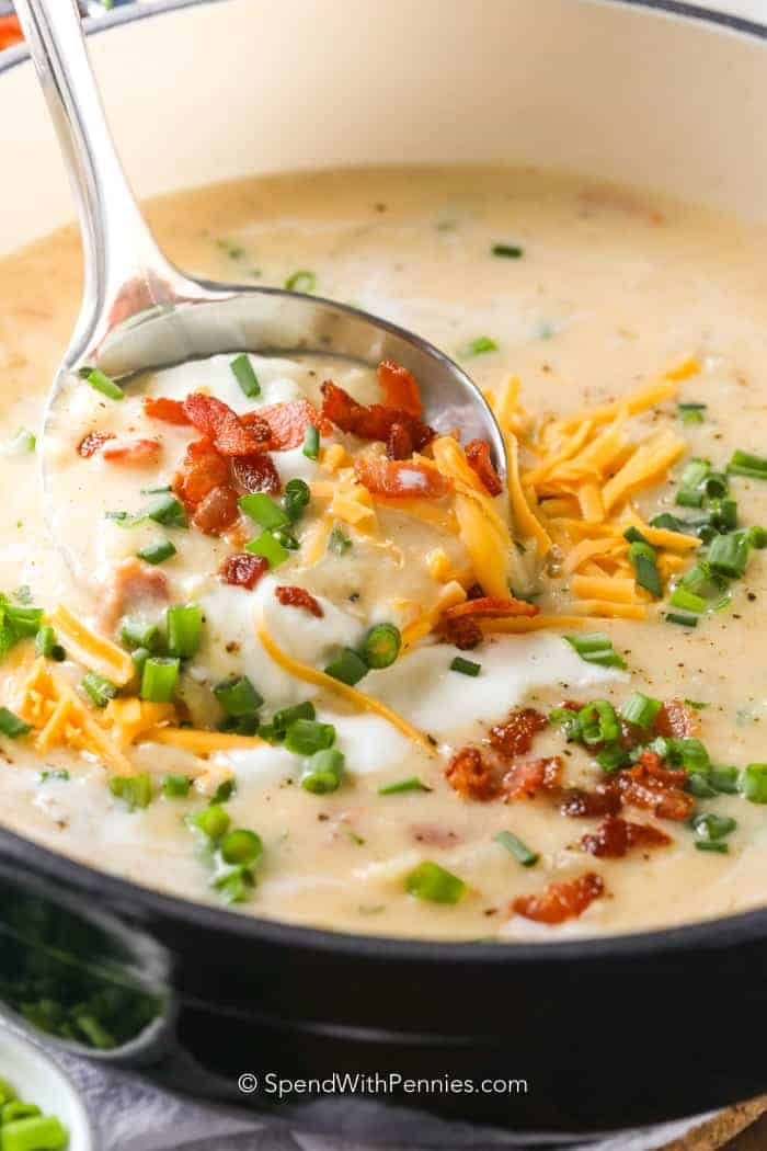 A ladle of baked potato soup with cheese, bacon and green onions.
