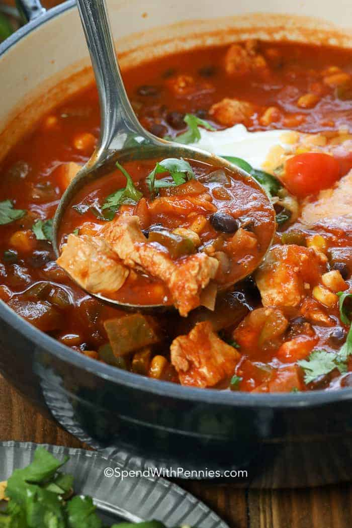 A ladleful of chicken taco soup in the pot