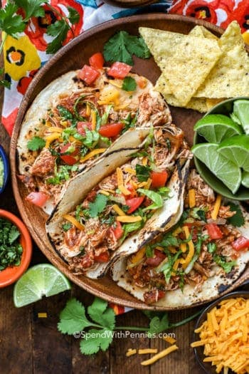 Crock-Pot chicken tacos on a wooden plate with lime wedges and tortilla chips
