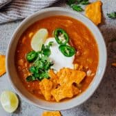 Easy Chicken Taco Soup in a bowl with jalapeno, sour cream and tortilla chips
